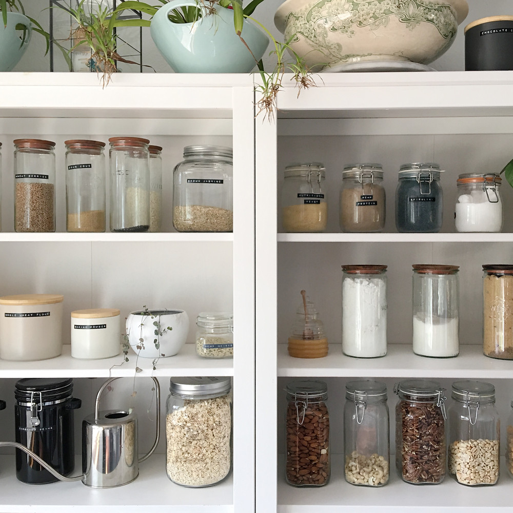 organized open pantry with glass jars, wood lids and plants
