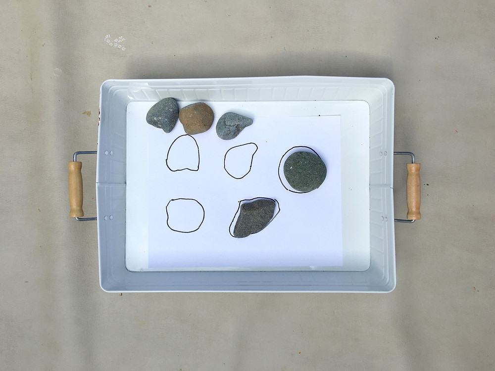 white tray with piece of paper, lines traced around rocks to create a matching game