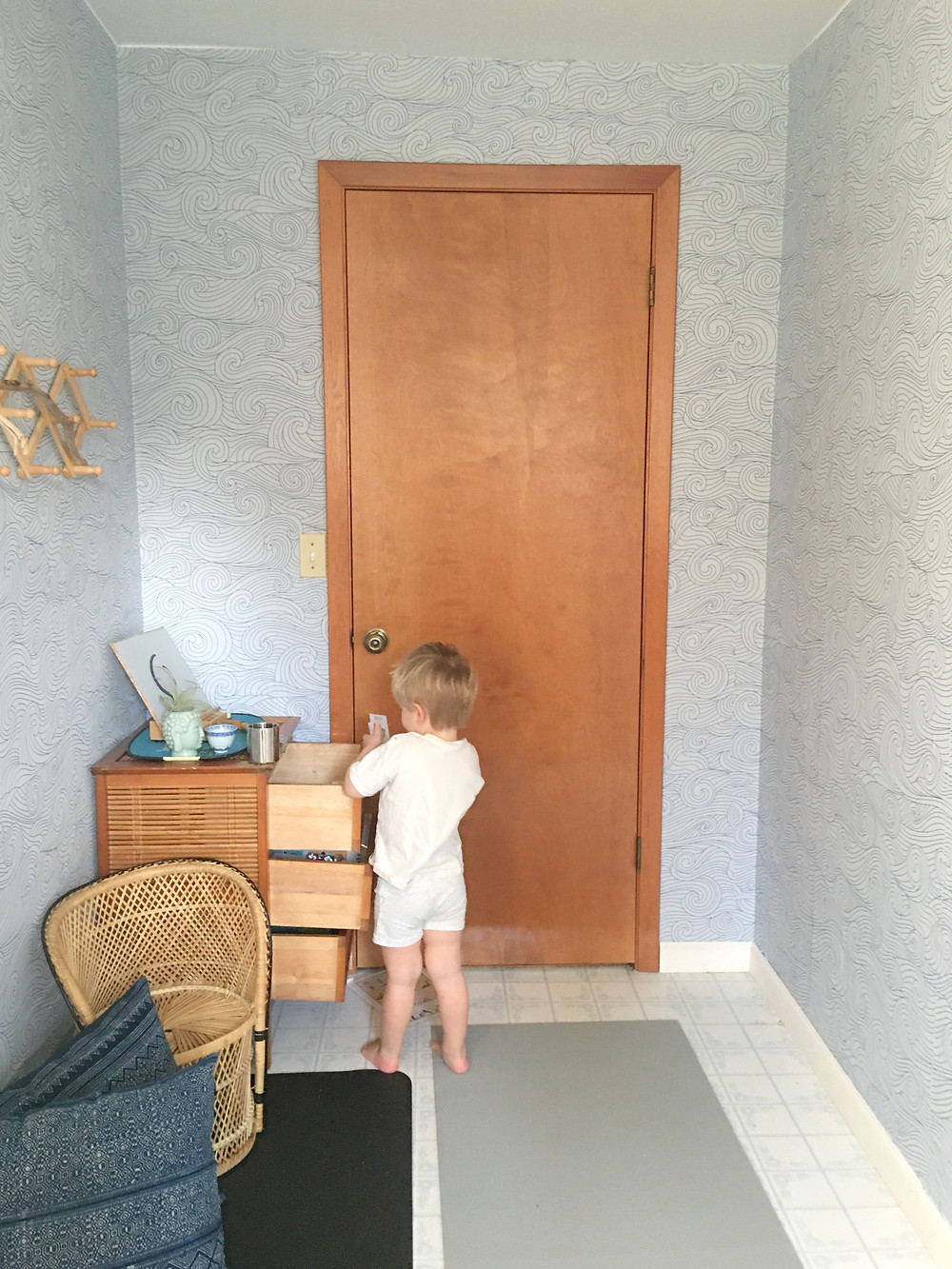little boy next to open drawers standing in front of a closed door in meditation room