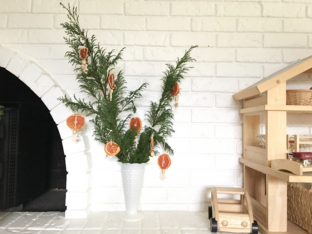 evergreen branches in a vase sitting near a fireplace with dried orange slice ornaments hanging from the branches
