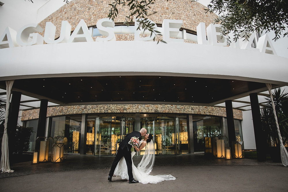 Front entrance to luxury wedding hotel Aguas de Ibiza. bride and groom kissing on wedding day