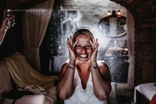 bridesmaids spraying hairspray onto bride backlit by flash in dark hotel villa