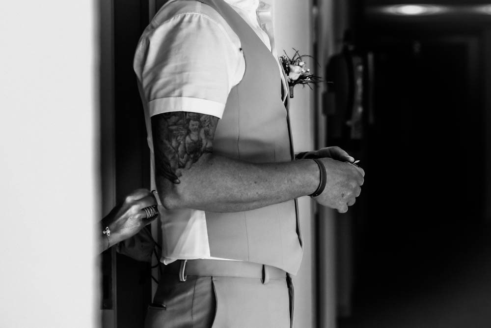 black and white photo First look at their Ibiza wedding,  side view of bride helping groom into his suit from behind