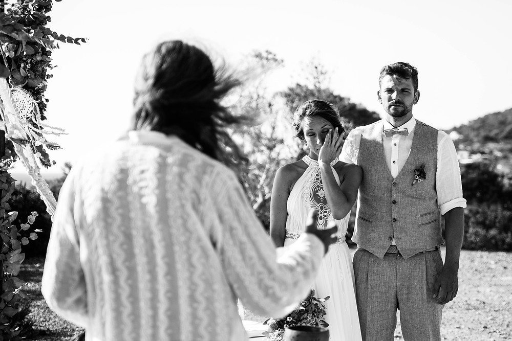 Black and white wedding photo of bride crying next to her groom at her ceremony in Ibiza