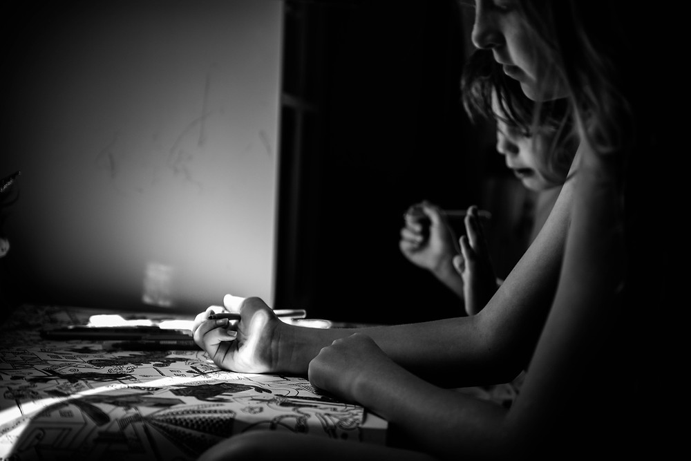 black and white photo of two young children colouring in on their colouring table next to a window letting the light in giving it a sultry moody feeling of the confinement of covid-19 pandemic