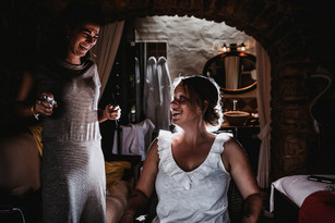 bride and maid of honour laughing and getting ready in dark rustic hotel room