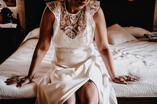 bride sitting on hotel room bed in vintage wedding dress