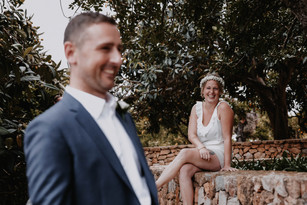 bride and groom getting ready together. bride looking at groom and laughing . intimate moment on wedding morning