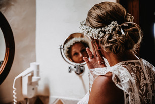 bride doing her hair in the mirror reflection wedding morning