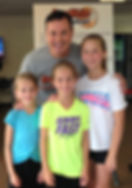 coach greg white posing with family of basketball campers