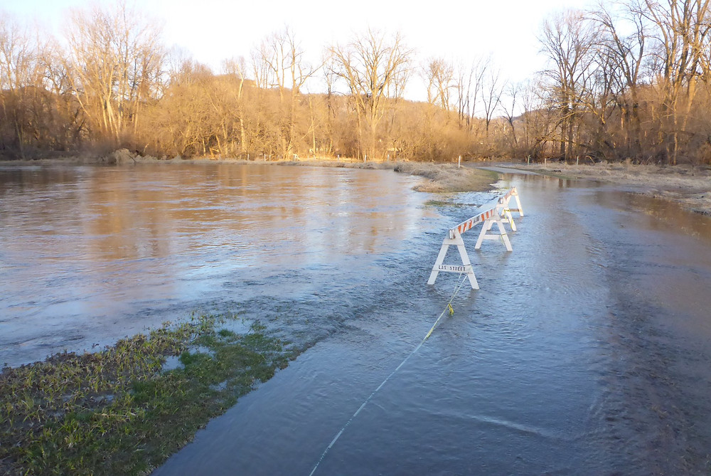 Marsh water flows over bike path during spring flooding
