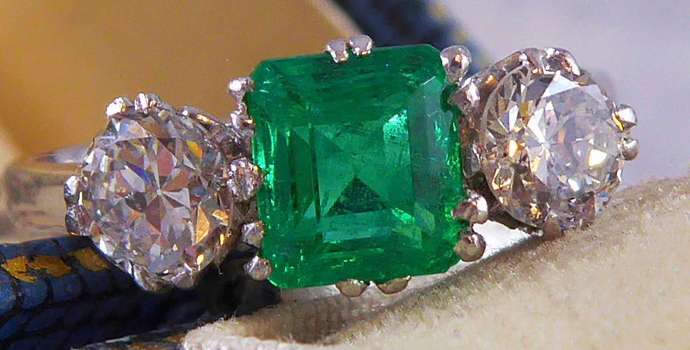 Vintage emerald and diamond ring shown in an antique ring box