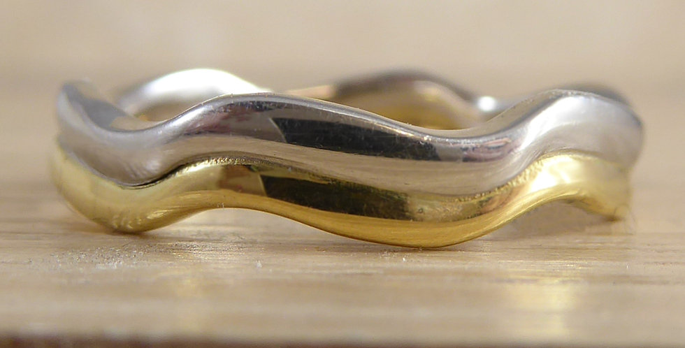 Contemporary shaped wedding ring on wooden display