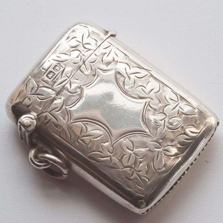 Edwardian silver vesta case opened to display the Birmingham Assay Office hallmark for 1908 together with the maker's mark. Note the stylized shield cartouch; this was often engraved with the wearer's initials or family crest.