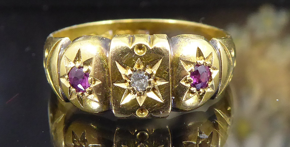 Antique gold with with diamond in the centre and ruby to each side