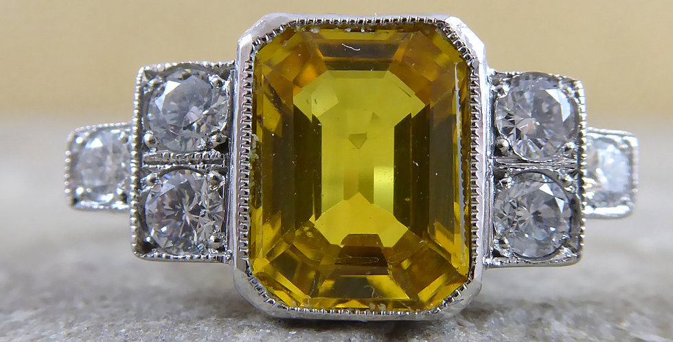 Yellow Sapphire ring in the Art Deco style with stepped diamond set shoulders