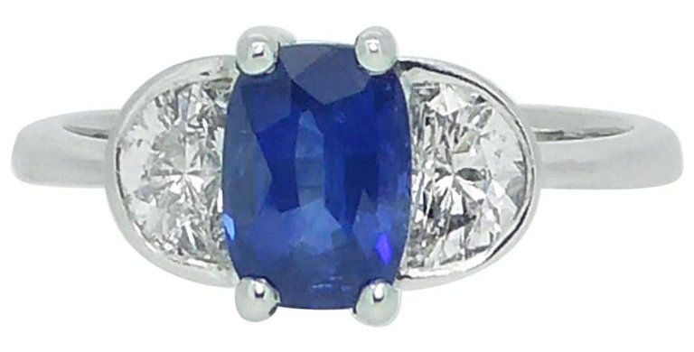 Sapphire and diamond ring with oval sapphire and two half-moon diamonds