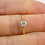 0.25 carat diamond in claw settings and yellow gold band on woman's hand