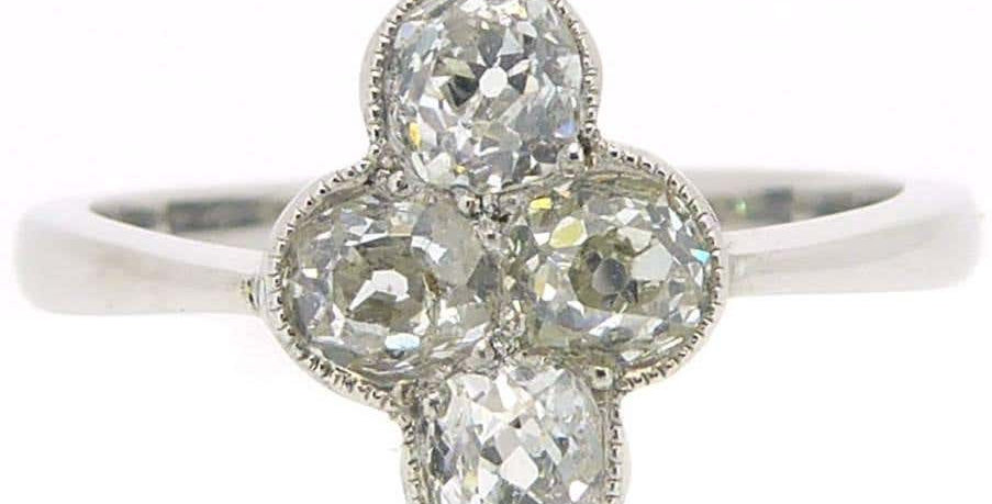 Antique old cushion cut diamond ring with four diamonds in a cross shaped cluster on white gold band