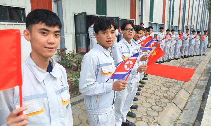 Các học viên VinFast vẫy cờ đón đoàn Triều Tiên trước nhà xưởng