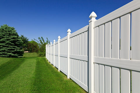 tall white fence next to a bright green lawn