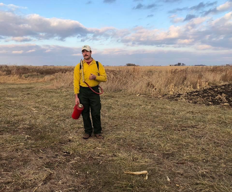 ISU Specialist teaching the group about prescribed prairie burning at an ISU Prairie STRIPS workshop.
