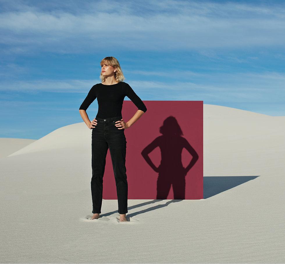 A woman standing in a desert landscape