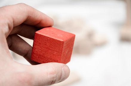 Doigts manipulant un cube rouge