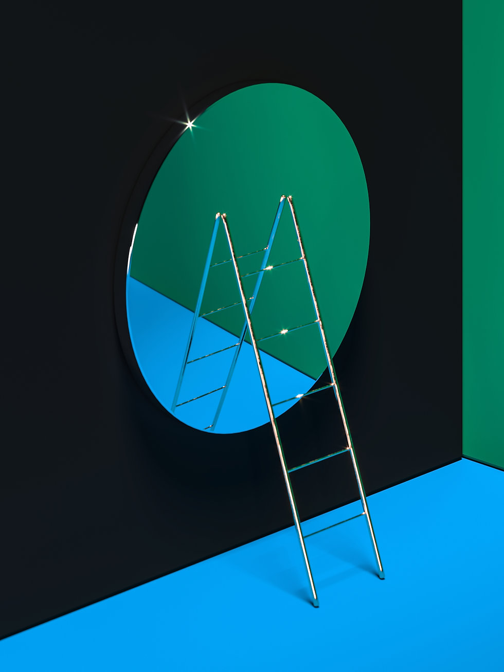 Shiny metal ladder leaning on a large round mirror