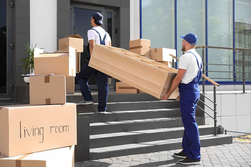Muuttomiehet kantaa kalusteita rivitaloon Helsingissä