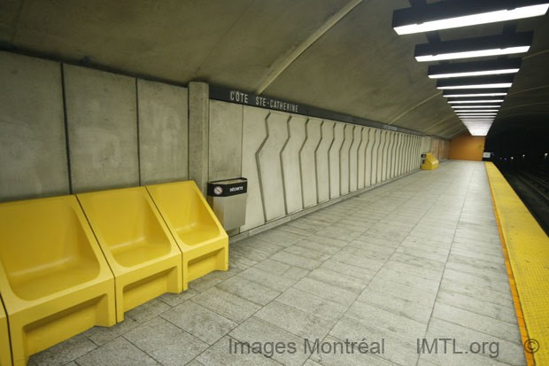metro station featuring three large yellow seats that are separated. Cote- Ste Catherine is written on the wall.