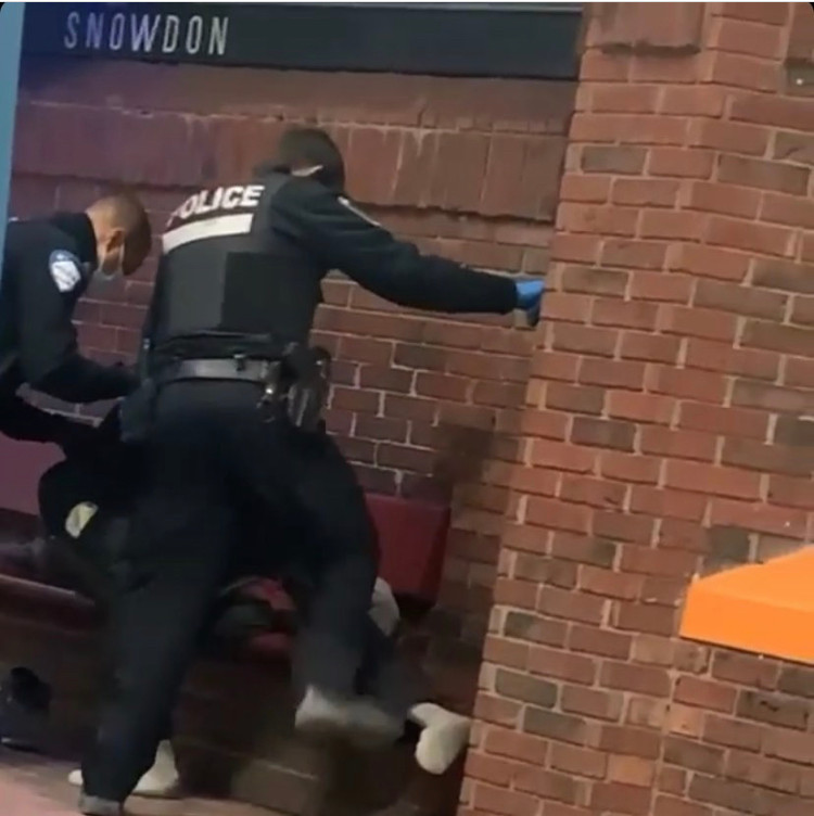 two police officers crowd a bench where a unhoused person is sleeping.