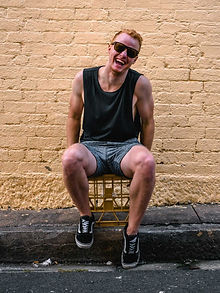 man-sitting-on-chair-beside-brick-wall-1