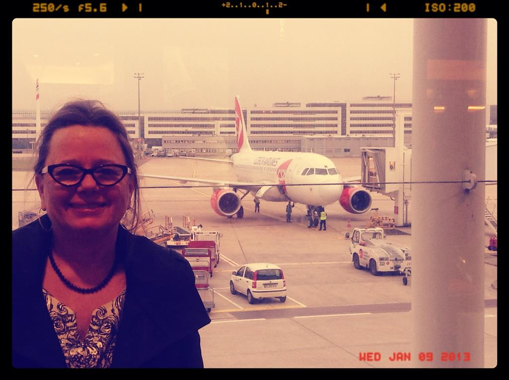 My mother, in Paris, about to board a flight to Prague.