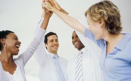 男性二人・女性二人のオフィス仲間が片手を上にあげタッチしている。成功を喜んでいる様子。
