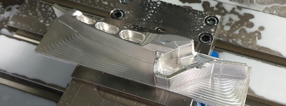 Sports car hood bracket after first machine operation