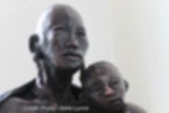 Maternité Masaï. Une mère Masaï tenant son bébé dans les bras et regardant l'avenir. Détail de l'oeuvre de 70 cm de haut en bronze