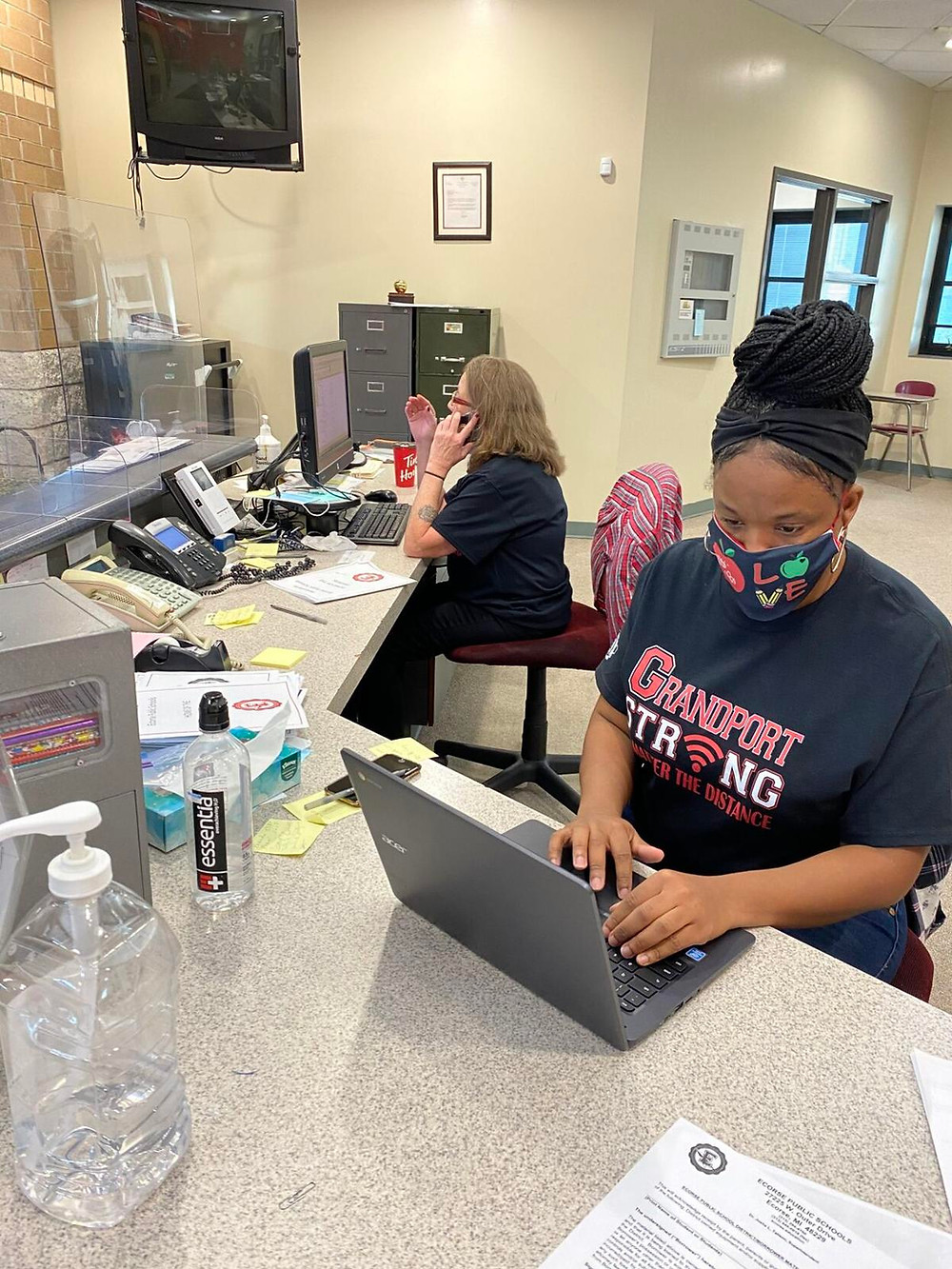 Toyre Burks, a teacher with Ecorse Public Schools, is aiding a student who is having difficulty logging on to Google Classroom. The district set up a hotline for parents and students. Photo courtesy of Ecorse Public Schools
