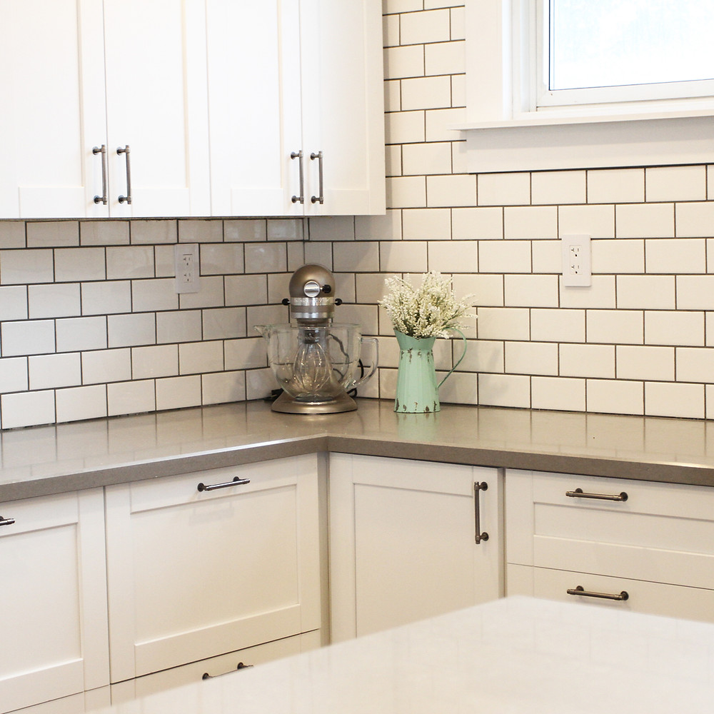 AFTER: A crisp white kitchen with a large, custom island with Shiplap. White subway tile with contrasting grey grout and grey quartz countertops complete the look.