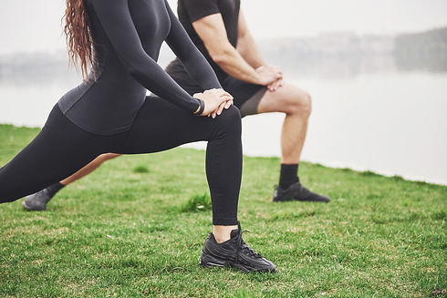 fitness-couple-stretching-outdoors-park-near-water-young-bearded-man-woman-exercising-toge