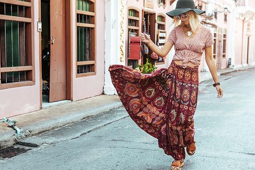 Boho girl in maxi skirt walking on the c