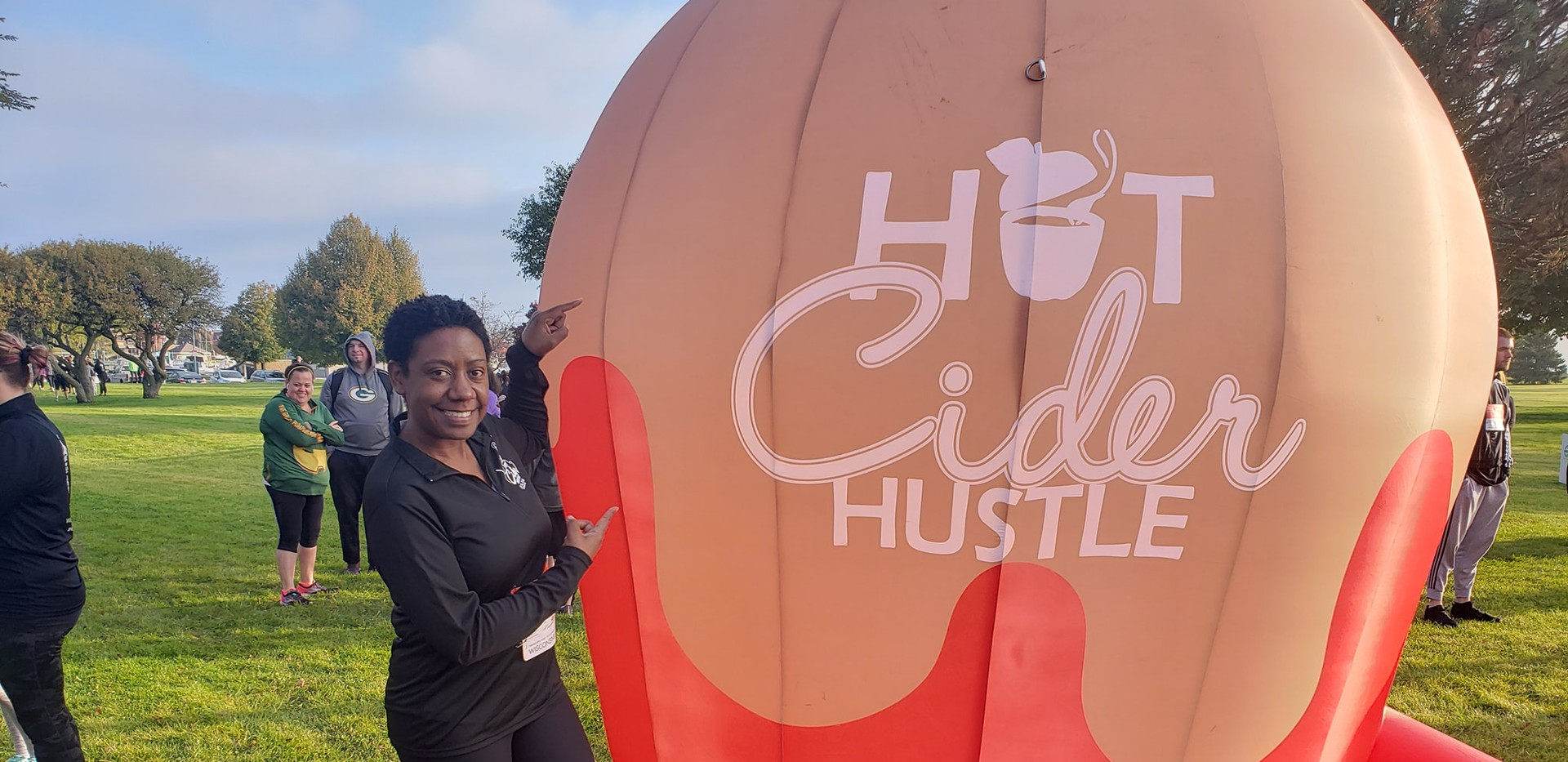Angela posing with the Hot Cider Hustle ballon