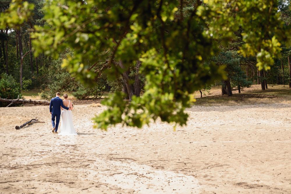 wandelend bruidspaar bij zandverstuiving