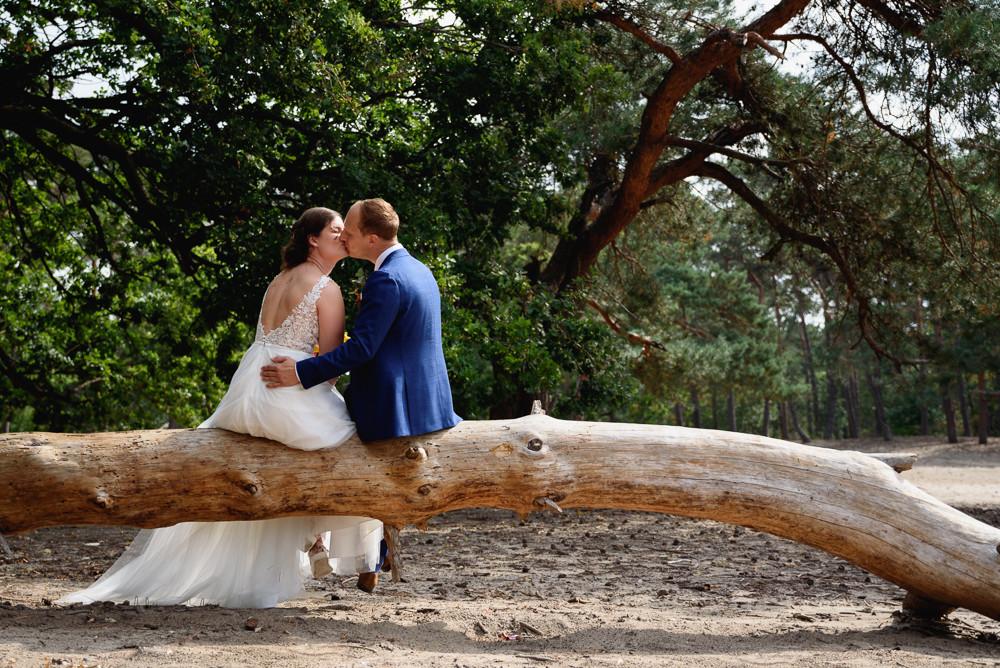 bruidspaar op boomstam bij zandverstuivi