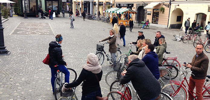 A group of active people cycling on bicycles doing a guided tour in Ljubljana.