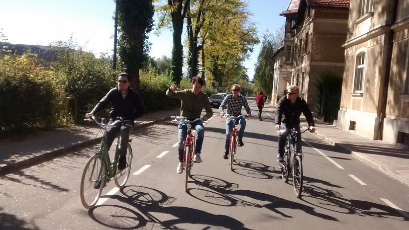 younger men cycling streets of Ljubljana on guided bicycle tour.