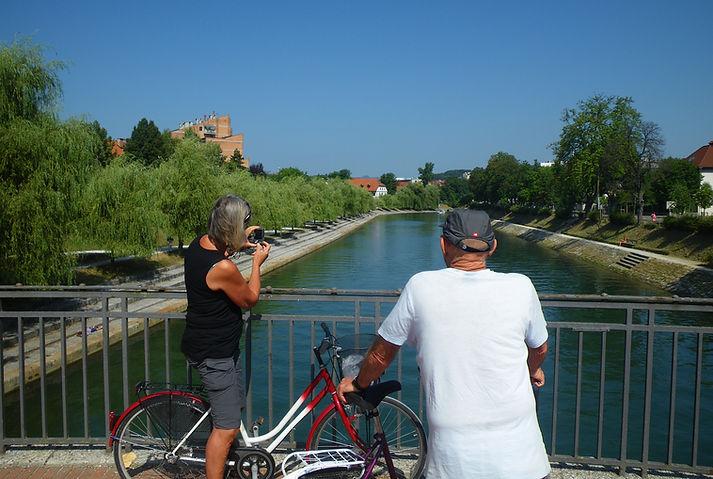 A couple on bicycles doing Ljubljana bike tour, exploring Slovenia.