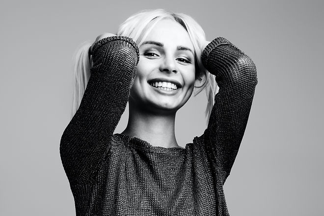 smiling-woman-holding-hair-on-both-hands