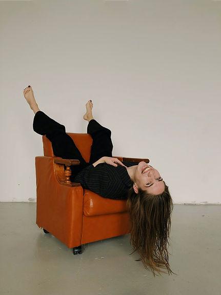 woman-in-sitting-upside-down-in-armchair