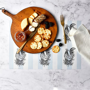 A cheese board with a beautiful paper placemat underneath.